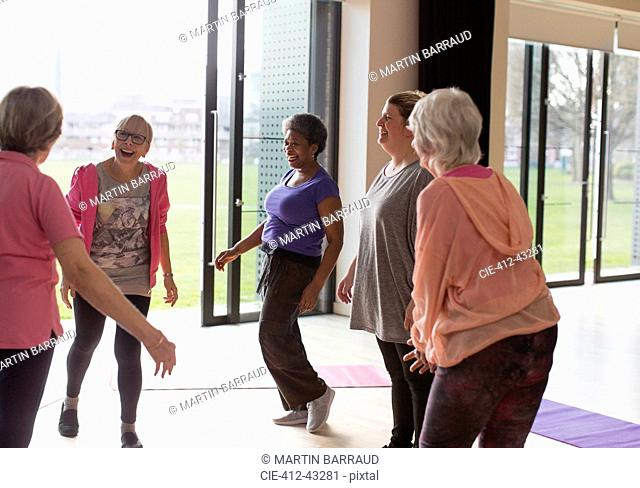 Smiling active senior women talking in exercise class