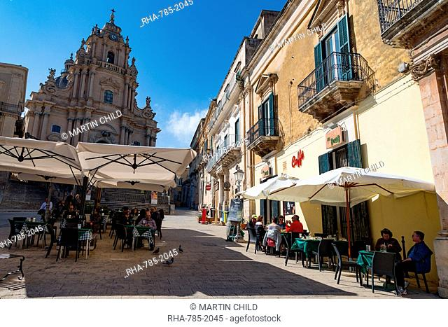 People dining in Piazza Duomo in front of Cathedral of San Giorgio in the historic hill town of Ragusa Ibla, Ragusa, UNESCO World Heritage Site, Sicily, Italy
