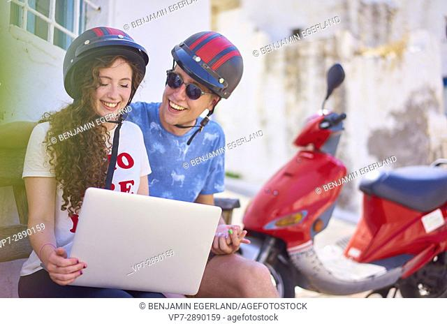 active young couple using mobile laptop during break at road trip with moped. Hersonissos, Crete, Greece