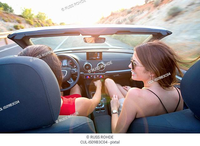 Rear view of two young women driving on rural road in convertible, Majorca, Spain