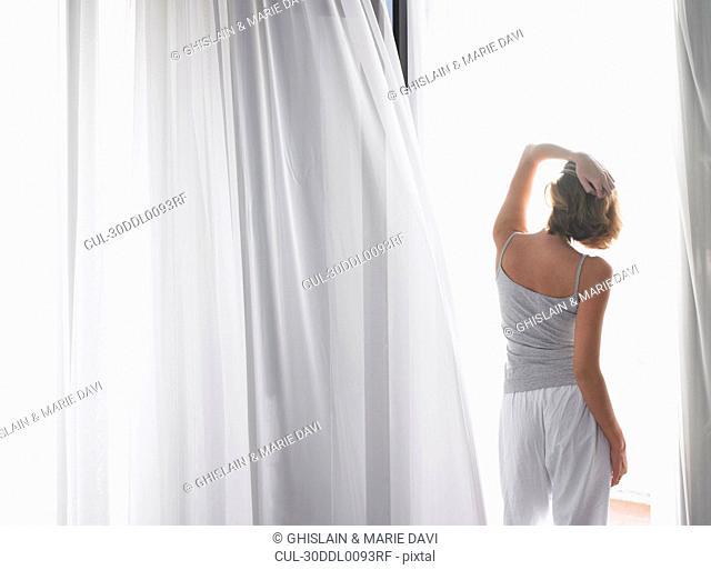 Woman in her pyjamas, on the balcony