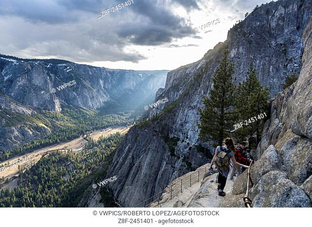 Group of hikers going down to Yosemite Point with the amazing view of the valley and the sunset, California, USA