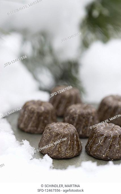 Mini chocolate Bundt cakes with a schnapps glaze on a tray in the snow
