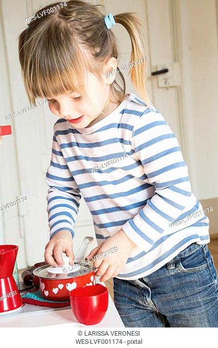 Little girl playing with children's kitchen