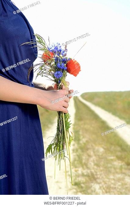 Woman holding bunch of field flowers, close-up