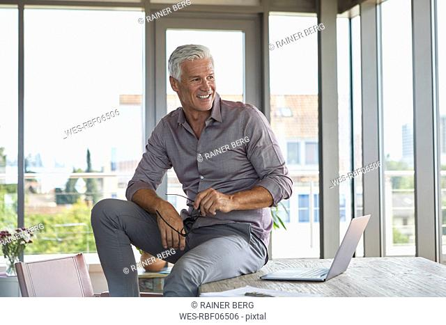 Smiling mature man with laptop sitting on table at home