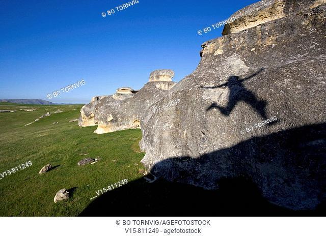 shadow of a woman jumbing on rocks