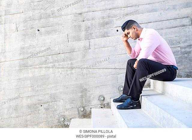 Stylish businessman wearing pink shirt sitting on steps in front of concrete wall