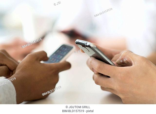 Close up of friends texting with cell phones at table