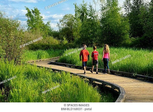 Children walking on wooden walkway in wetland marsh