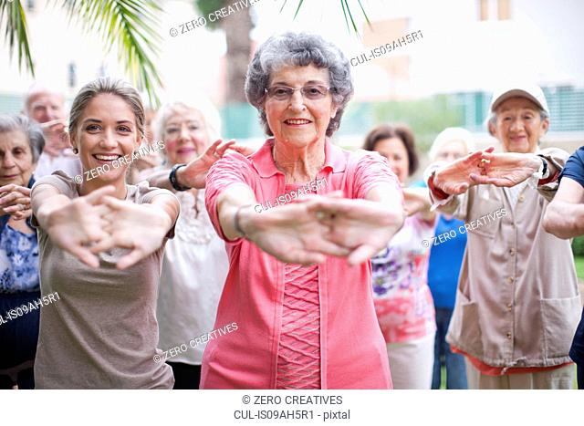 Medium group of seniors exercising in retirement villa garden