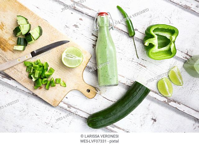 Glass bottle of homemade green Gazpacho and ingredients