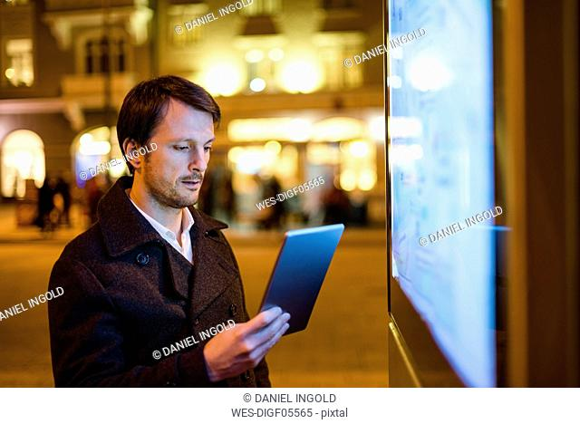 Businessman using digital tablet at night in the city