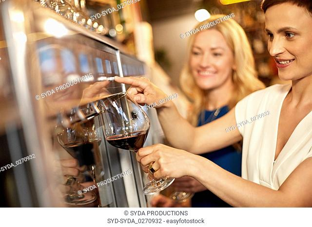 happy women pouring wine from dispenser at bar