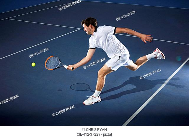 Male tennis player playing tennis, reaching with tennis racket on tennis court
