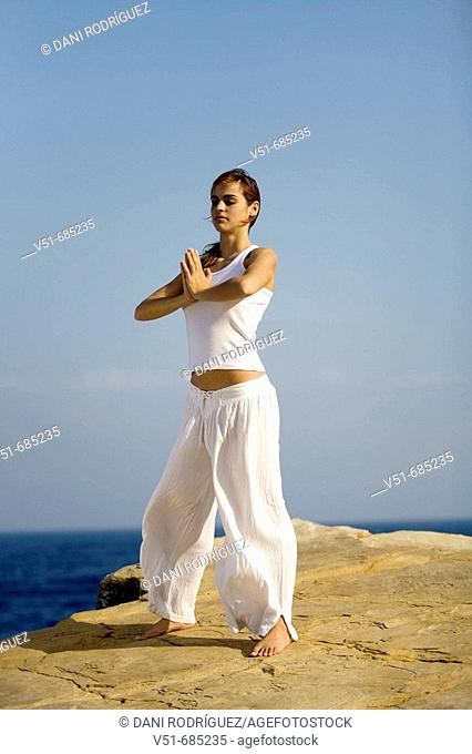 Woman doing yoga by the sea
