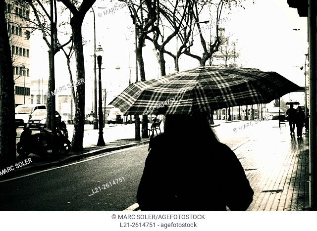 Woman with umbrella in a street. Barcelona, Catalonia, Spain