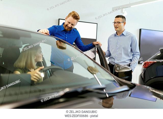 Salesman advising customers in car dealership