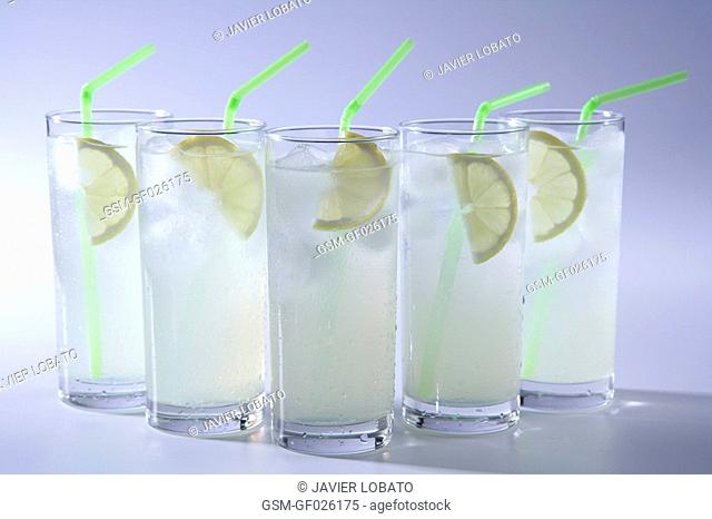 Lemon soft drinks in tall glasses with lemon slice and green straw