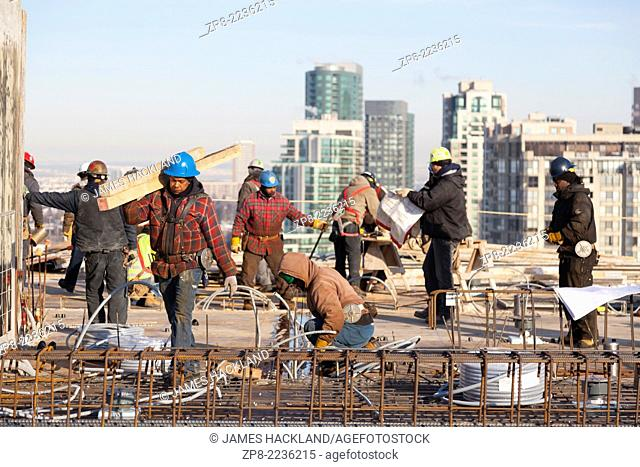A construction worker carrying a load of wood with other workers in the background on a rooftop construction site in Toronto, Ontario, Canada