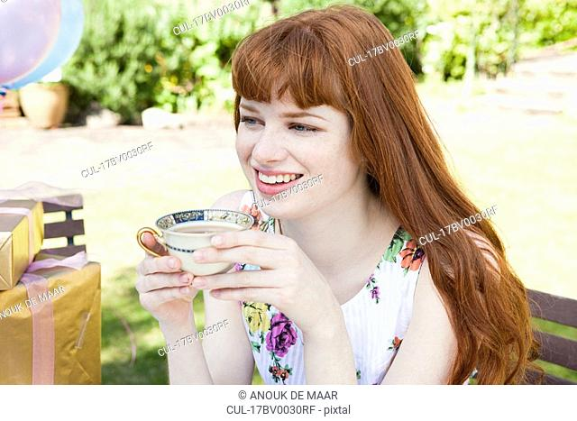 young woman holding tea cup, smiling