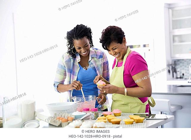 Mother and adult daughter baking cupcakes in kitchen