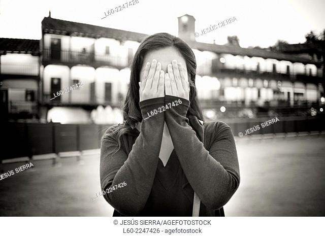 Girl with hand over eyes, Chinchón square, Comunidad de Madrid, Spain