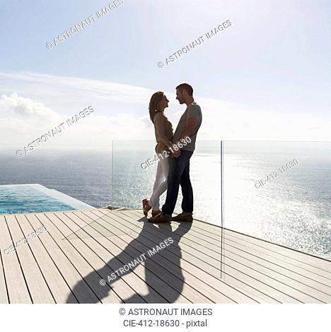 Couple on modern balcony overlooking ocean