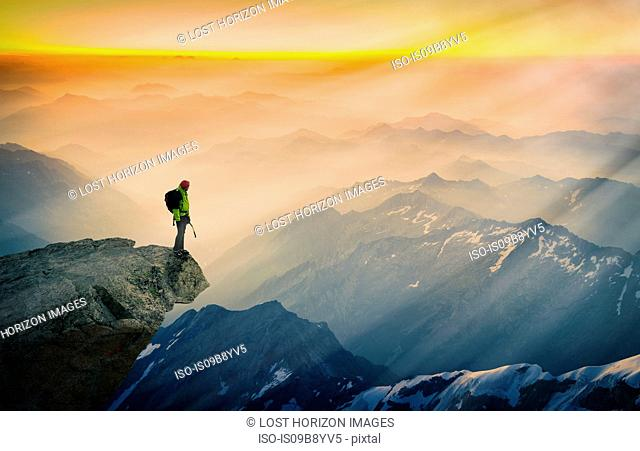 Mountain climber standing on edge of mountain, looking at view, Courmayeur, Aosta Valley, Italy, Europe