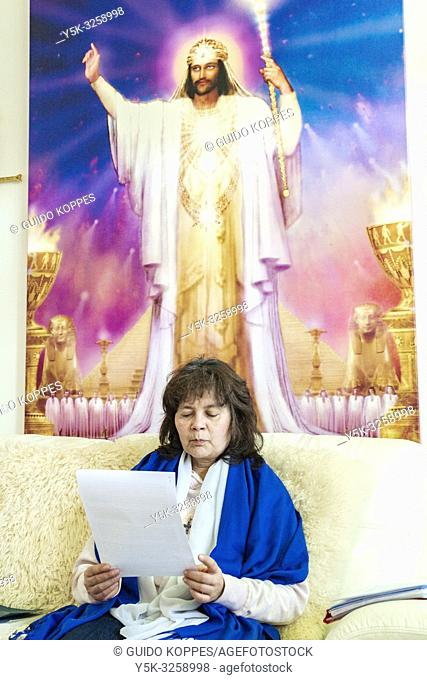 Dongen, Netherlands. Female follower of a spiritual, religious leader sitting down on a huge couch and enjoying an Angel Service of prayer and meditation given...