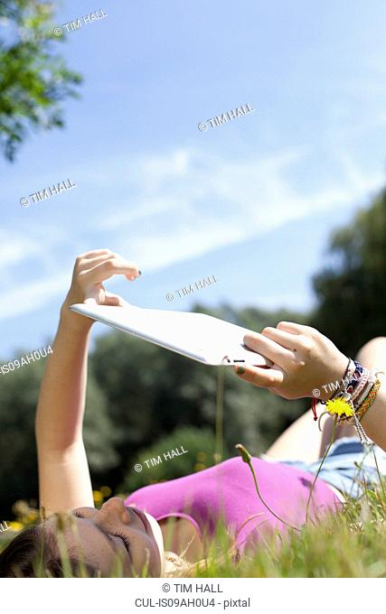 Teenage girl lying in park looking at digital tablet
