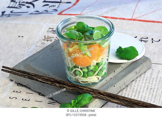 Ingredients for Asian noodle soup with vegetables layered in a glass