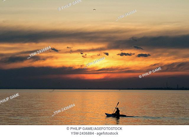 Person kayaking on Port Phillip Bay at sunset, Melbourne