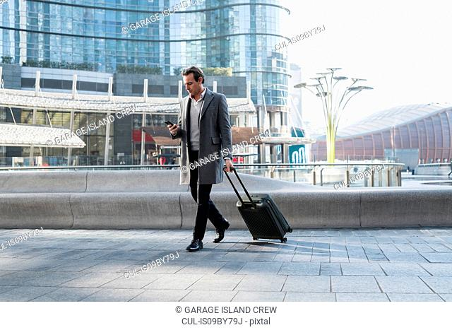 Businessman with wheeled luggage, using smartphone in city centre, Milan, Lombardia, Italy