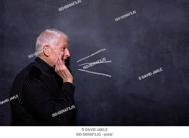 Portrait of senior man in front of blackboard