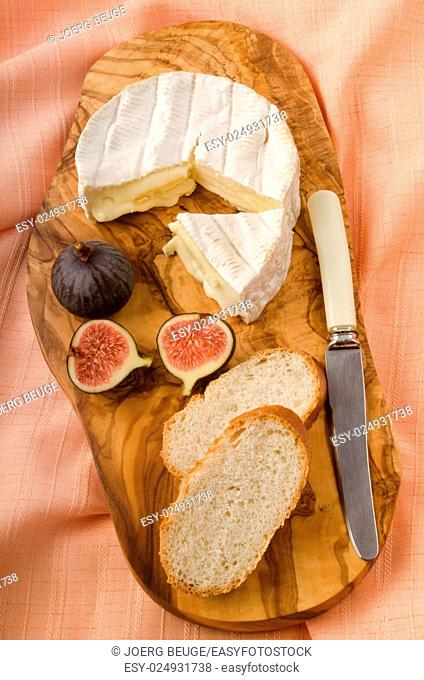 camembert with fig, bread and knife on wooden board