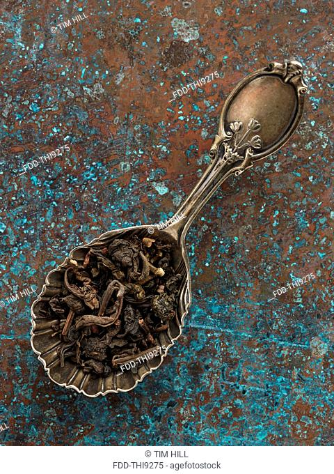 Oolong tea leaves in an antique tea caddy spoon