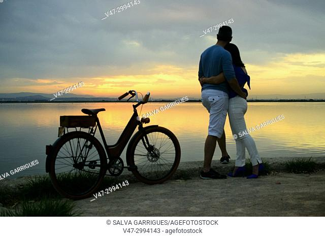 A wedding couple arrives by bicycle to the Albufera Natural Park to see the sun gate