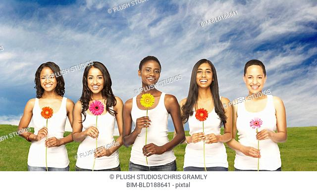 Multi-ethnic friends holding daisies