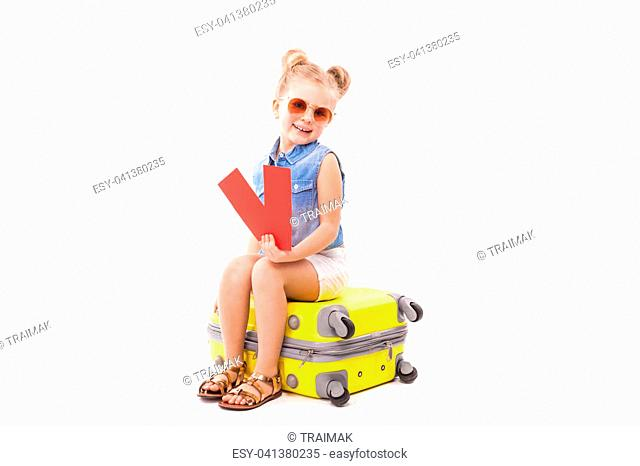 Isolated on white, pretty little caucasian blonde girl in blue jeans shirt, white shorts, sunglasses and sandals sit on the yellow suitcase, hold two red cards