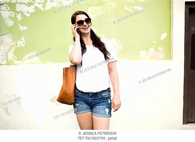 Woman talking on mobile phone in front of old wall