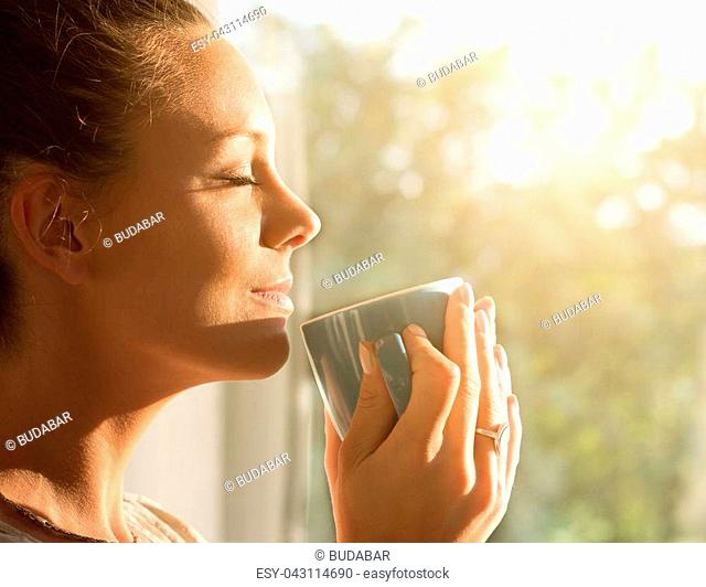 Pretty young woman enjoying first morning coffee on sunshine by window