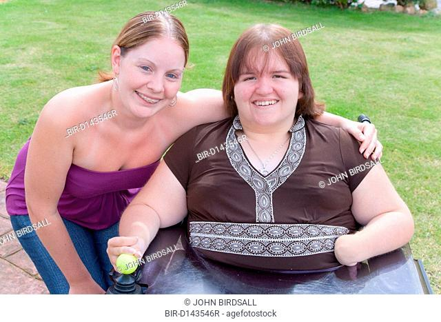 Woman with a disability and her non disabled friend out in the garden