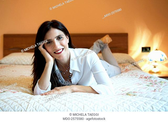 Smiling woman lying down on a double bed. Como (Italy), 13/08/2014