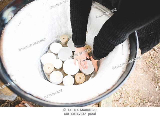 High angle view of young woman arms reaching into barrel kiln for clay pot