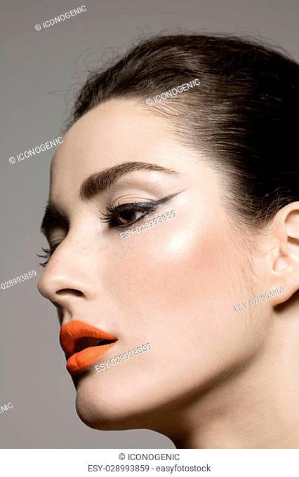 Model wearing eyeliner and orange lipstick