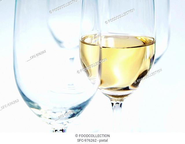 Two empty glasses and a glass of white wine