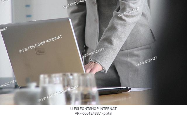 TU, TD, Medium shot, Businesswoman giving a presentation using a flipchart and laptop