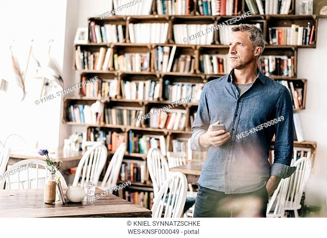 Mature man standing in cafe