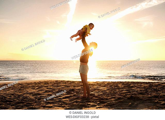 Mother lifting up little daughter on the beach at sunset
